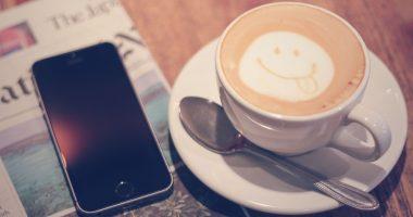 オシャレなカフェでインターネットビジネスの副業をしている。スマイルの描かれたコーヒーとスマホが机に並んでいる
