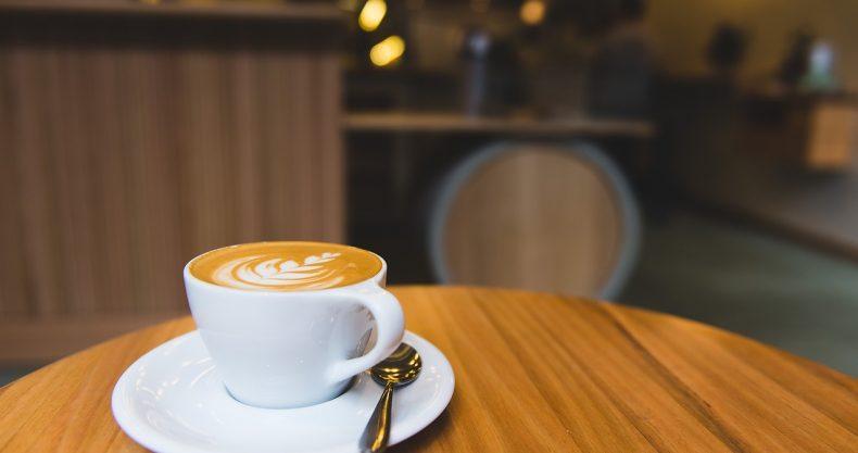オシャレなカフェでインターネットビジネスの副業をしている。丸いテーブルの上にカフェラテが置かれている