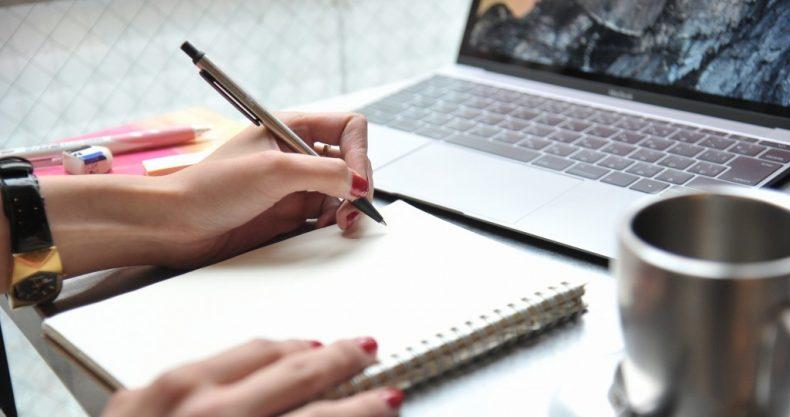 パソコンを前に、ネイルをした女性がメモを取る。