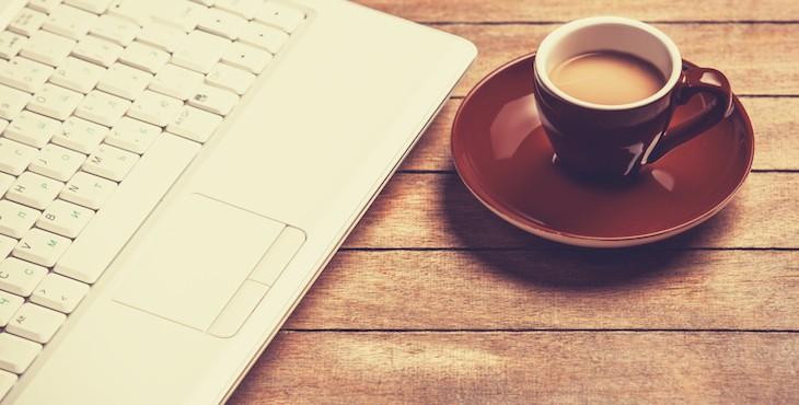 パソコンとミルクココアの写真。カフェでインターネットビジネスの副業