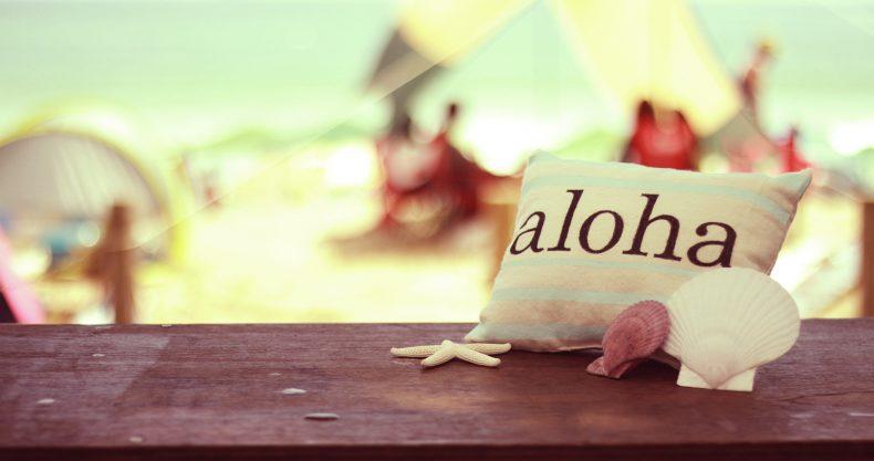 alohaと書かれたミニクッションの後ろには綺麗な海